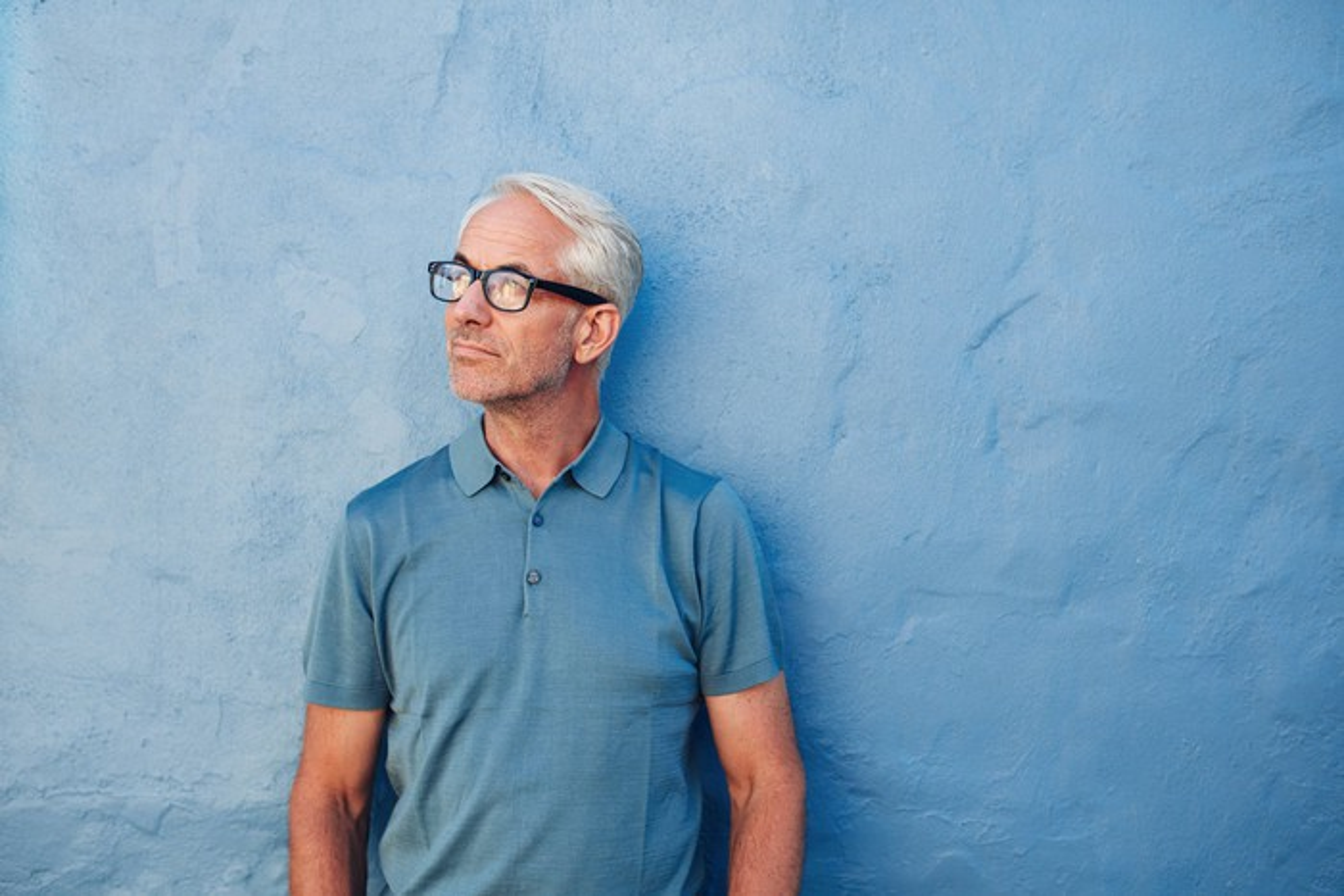 Older man wearing eyeglasses standing against a blue background