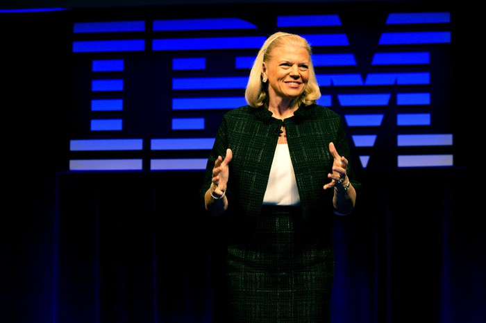 IBM CEO Ginni Rometty speaking at a conference, with the IBM logo in the background.