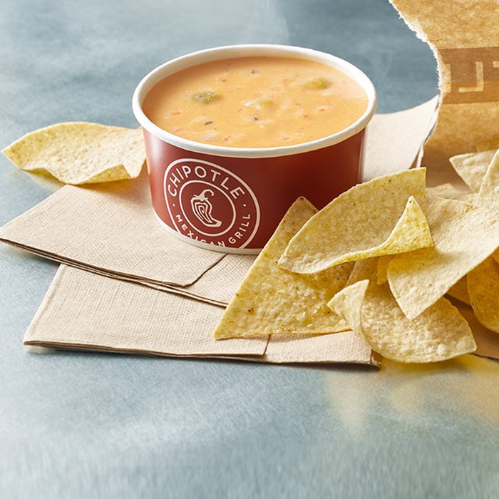 A cup of Chipotle's queso with chips on the side