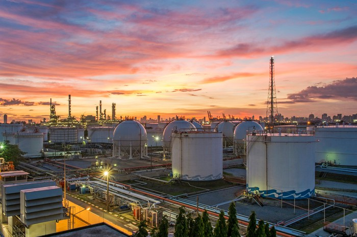 A refinery in the distance at sunset.