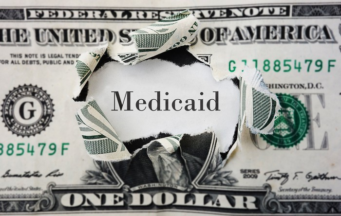 """A dollar bill with George Washington's face removed and replaced with a piece of paper reading """"Medicaid."""""""