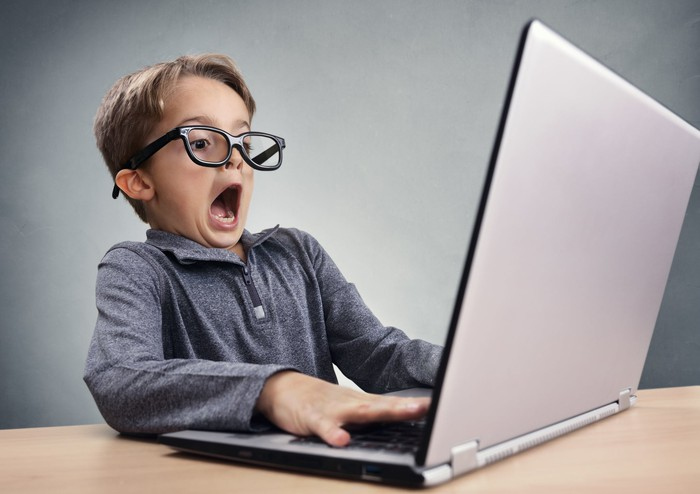 Boy in glasses at laptop, mouth agape in astonishment