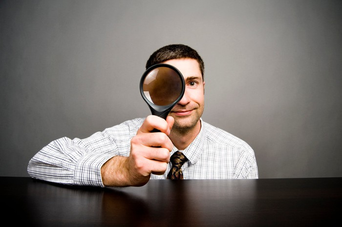 Man looking through big magnifying glass
