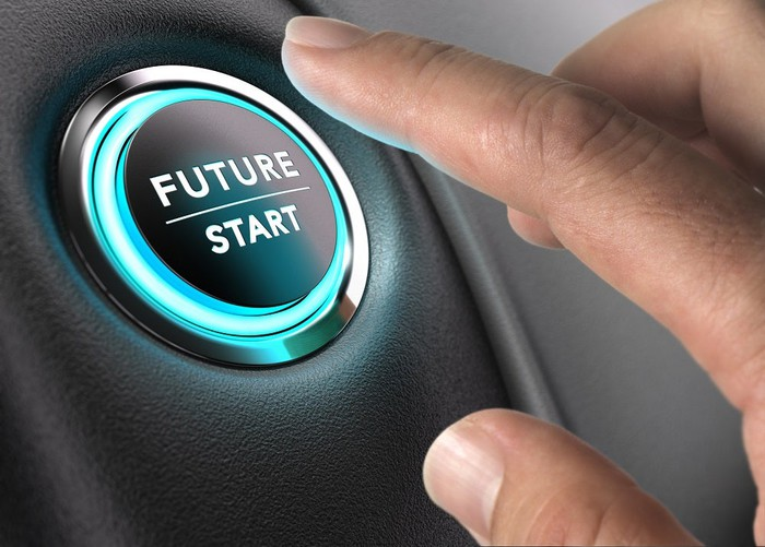 """A hand reaches to press a glowing button with """"Future"""" and """"Start"""" written on it."""
