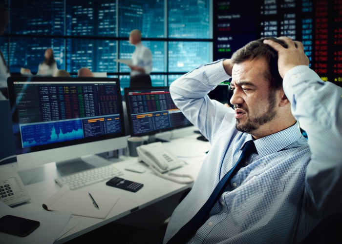 A frustrated stock trader grasping his head in front of computer screens.