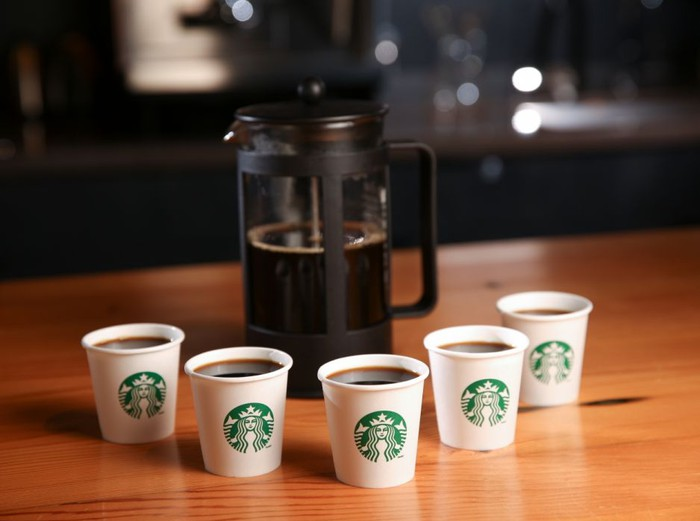 5 cups of Starbucks coffee around a French press