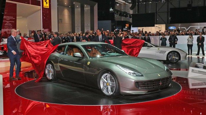 Someone pulling the cover off a Ferrari GTC4Lusso on a showroom floor.