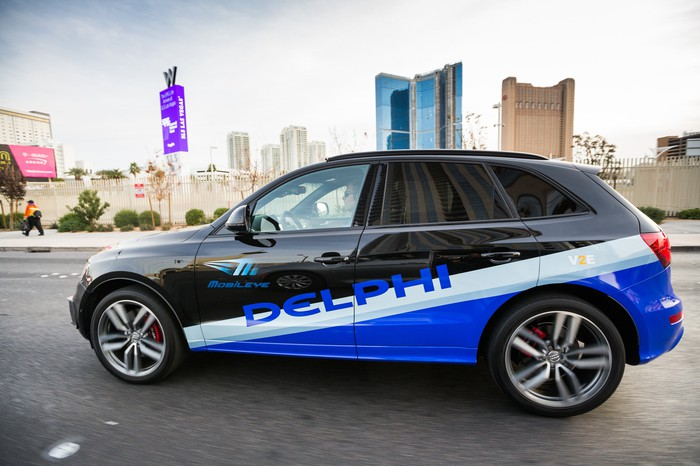 An Audi SUV with Delphi and Mobileye logos is shown driving in Las Vegas.