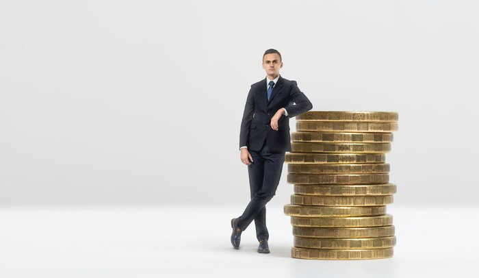 A businessman leans on a stack of giant gold coins.