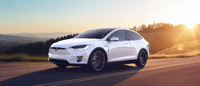 A white Tesla Model X can driving down a sun-drenched road.