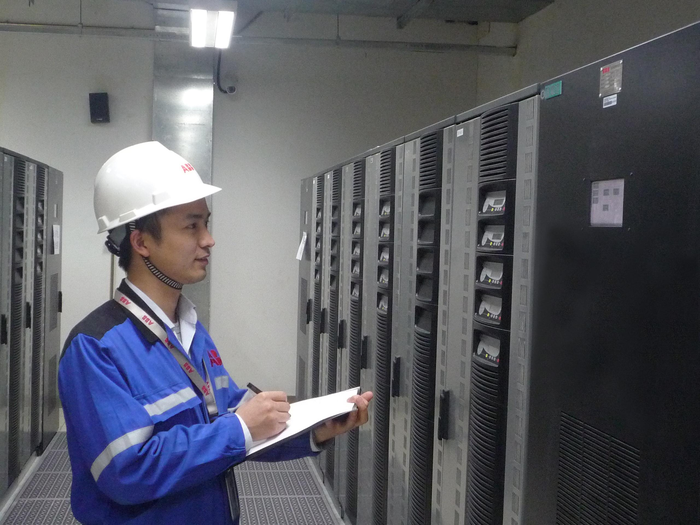 An ABB technician surveying some power conditioning equipment