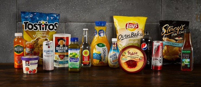 Assortment of 15 snack and beverage products on a table, including Tostitos, Lay's potato chips, an Izze beverage, Quaker Oats, Tropicana orange juice, Stacy's Pita Chips, and Sabra hummus.
