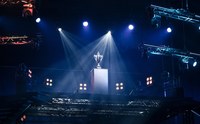 A trophy under spotlights on a stage.