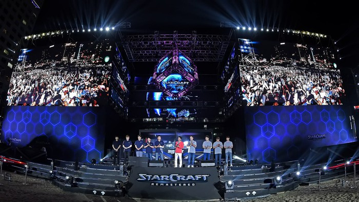 "Two teams on a stage at a competitive ""Starcraft"" event."