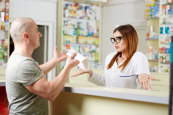 Pharmacist holding hands out with unhappy customer