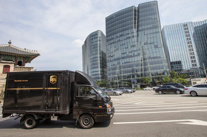 A UPS truck is parked outside an office building