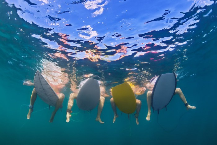 Surfers sitting on their boards with their feet in the water, as seen from below.