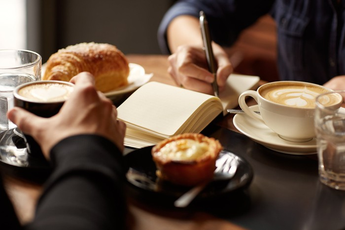 Pastries and coffee are seen at a table between two people facing each other.