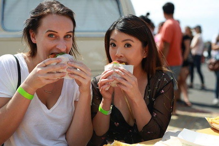 Two women eating Shake Shack burgers at an outdoor location.