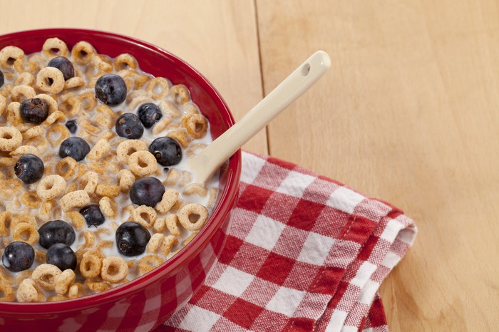 A bowl of cereal on a table with a napkin.