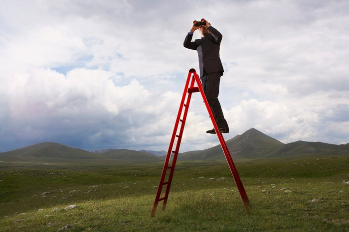 In a hilly landscape under a cloudy sky, man in a suit is standing on a ladder and looking into the far-off distance with a pair of binoculars.