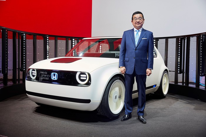Hachigo, in a blue suit, stands next to the Urban EV Concept, a white hatchback with styling reminiscent of 1970s Honda Civics, on Honda's stand at the 2017 International Motor Show in Frankfurt, Germany.