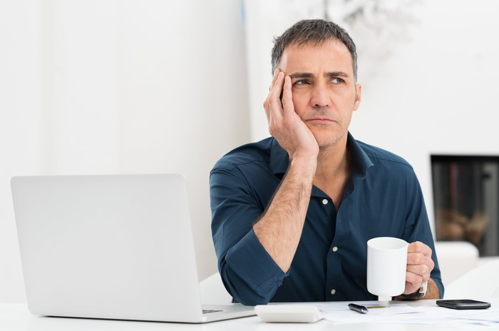 A worried man holding his head in his hand and pondering the future in front of his laptop.