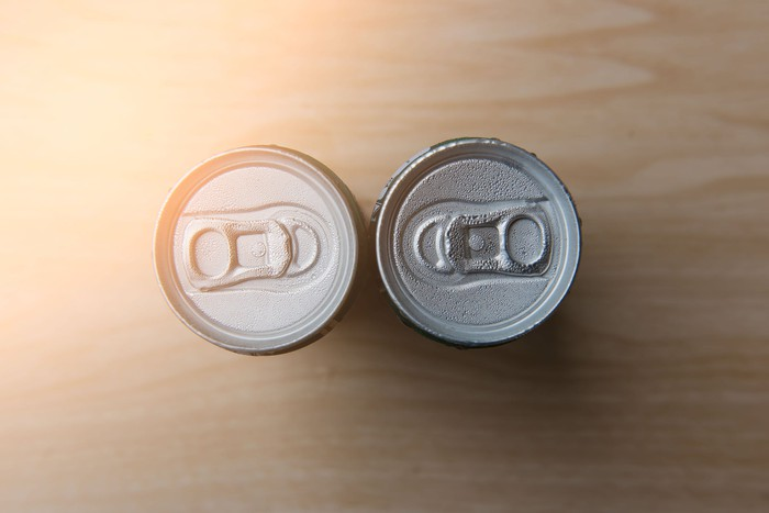 Two beverage cans sit facing each other on a table, as seen from above.