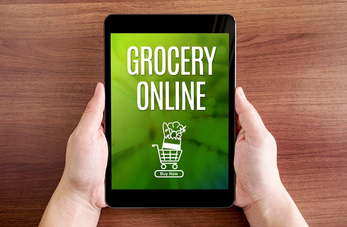 "Two hands hold a tablet showing the words ""grocery online"" and a graphic of a filled shopping cart."