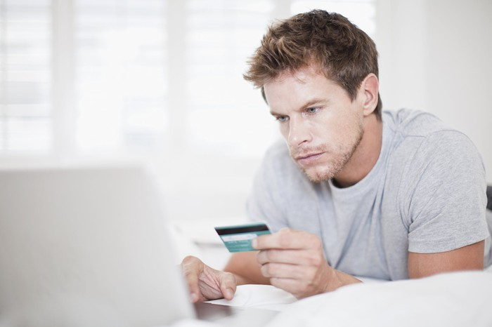 Man holding card and using computer