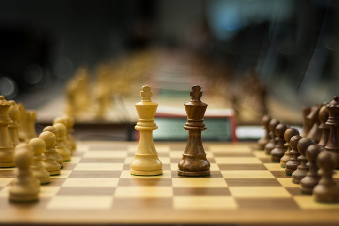 Two chess piece kings on a chessboard adjacent to each other