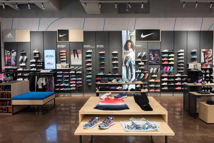 Interior of a Finish Line store with shoes lined up neatly on a wall display