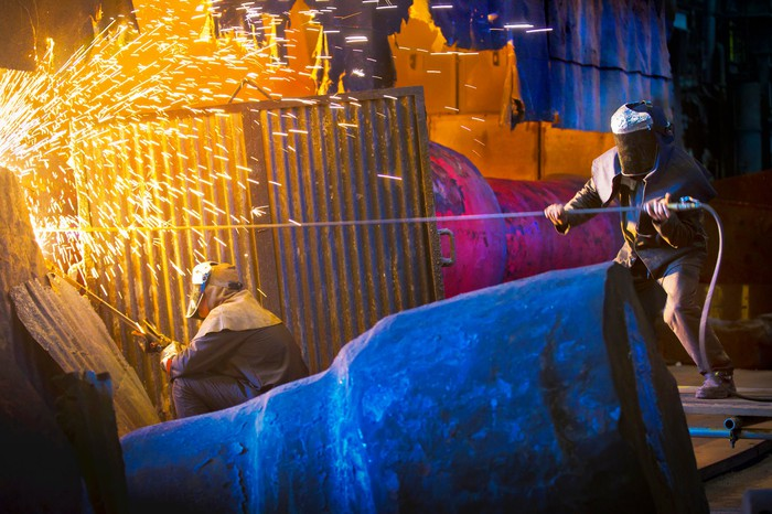 Two people working in a steel mill as sparks are flying.