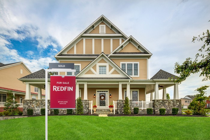 """A Redfin """"For Sale"""" sign in front of a house."""