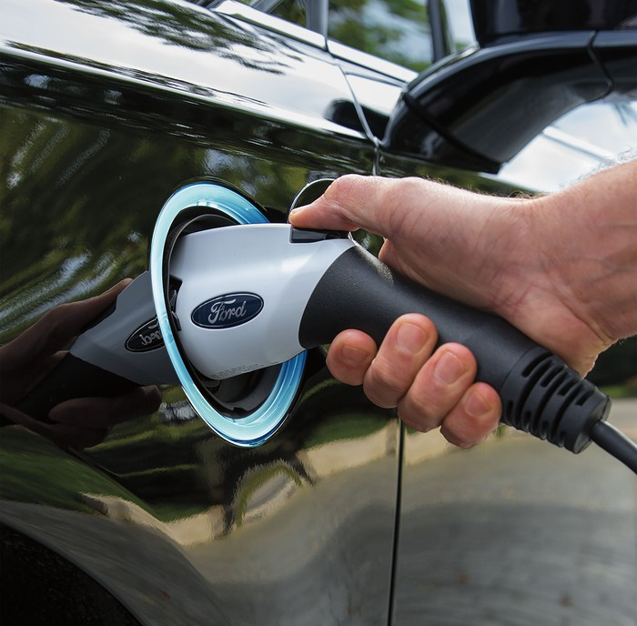 A close-up of a Ford-branded recharging plug plugged into a Fusion Energi hybrid sedan. Image source: Ford Motor Company.