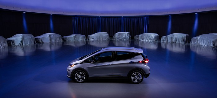 A silver Chevrolet Bolt EV is parked on a stage, with 9 vehicles covered in white sheets arrange in a semicircle behind it.