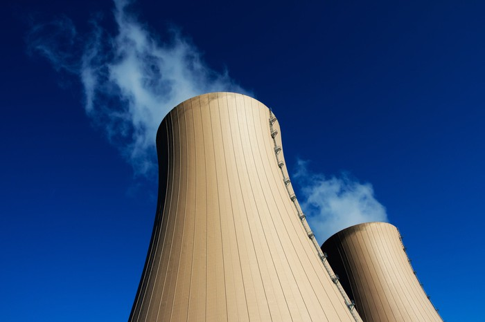 Two cooling towers shown against a clear blue sky.