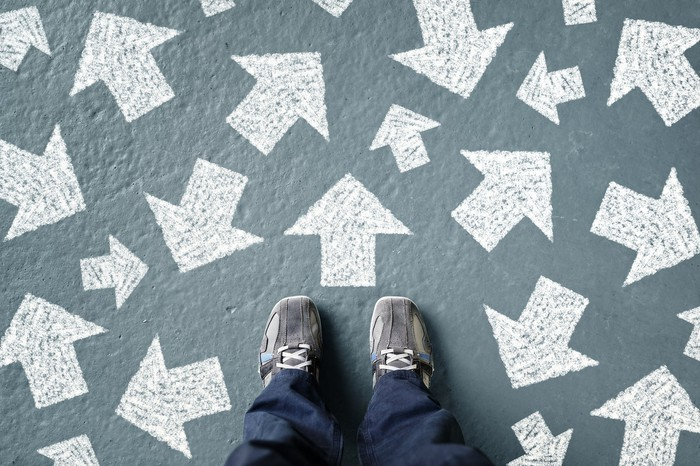 The image is the point of view of someone looking down at their feet. The green cement floor is covered in white arrows pointing in random directions.