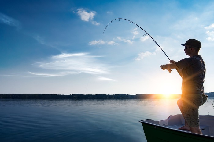 A man reels in his fishing line as the sun sets in the background.