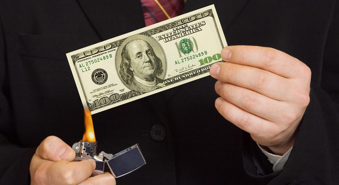 Man in dark suit lighting $100 bill on fire with a lighter.