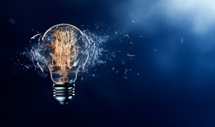 Edison-style light bulb shattering in front of a blue background