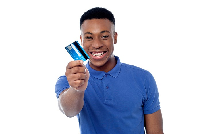 Young man smiling and holding up a credit card.