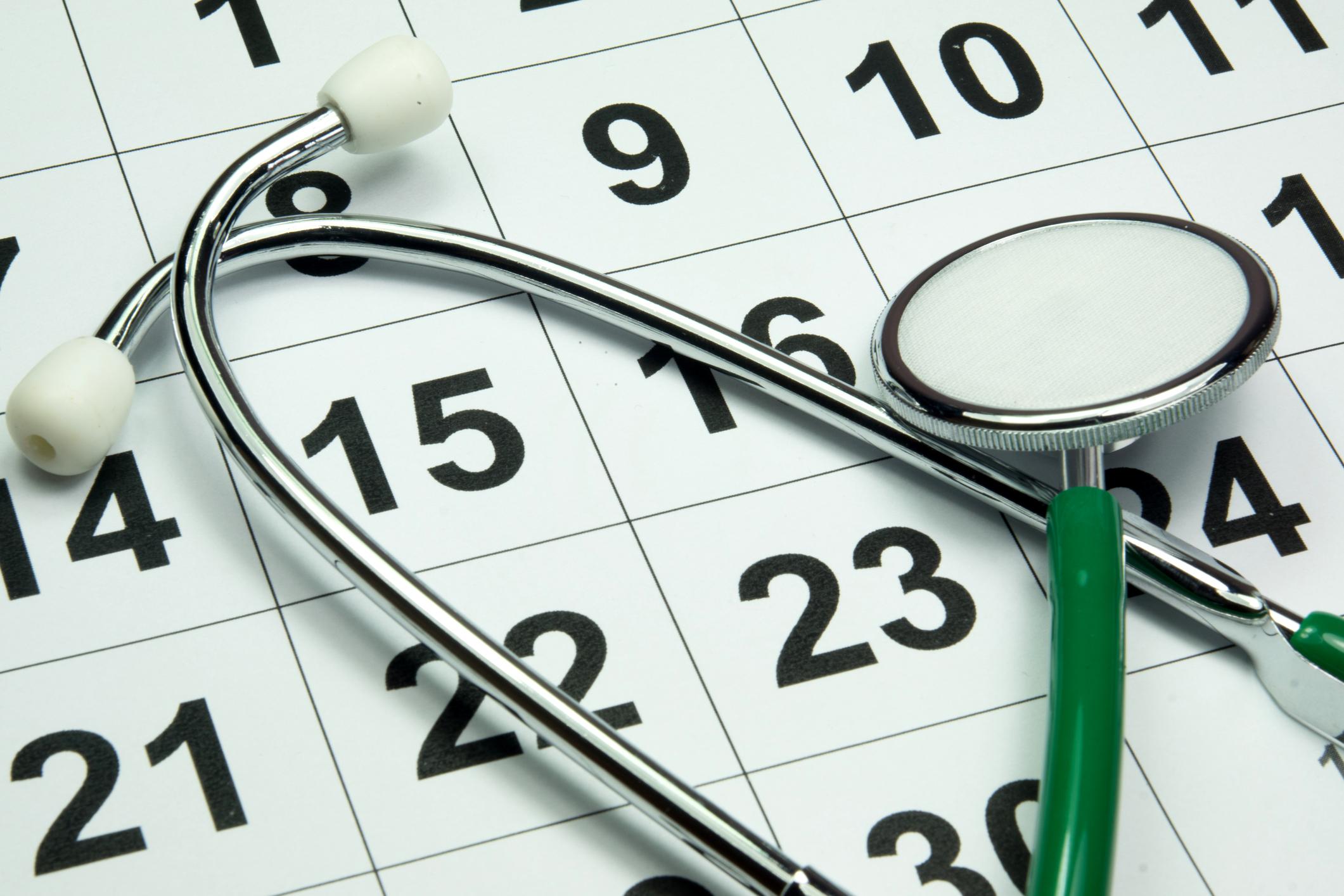 A stethoscope lying atop a calendar.