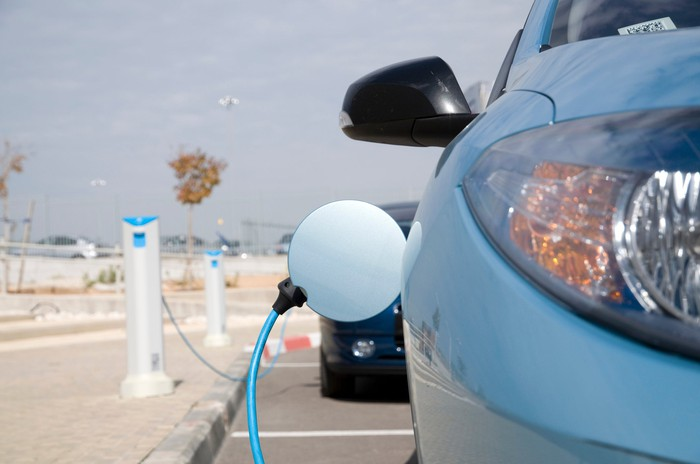 Electric car charging at an outdoor charging station.