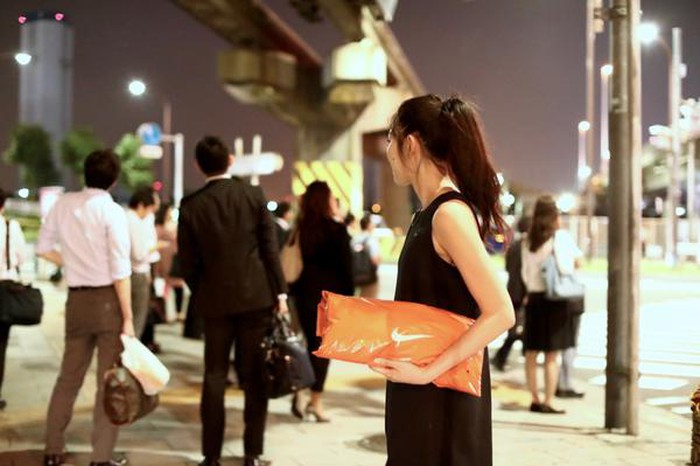 Woman in Japan on a busy sidewalk at night holding a bright orange Nike package.