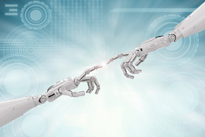 Two robot hands connecting at the fingertips.