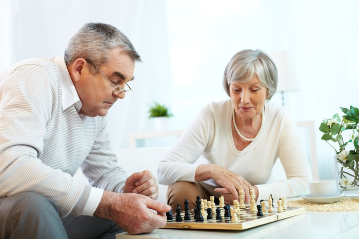 An older couple sits at a table playing chess.