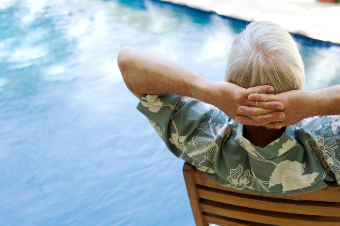 An elderly man relaxes by a pool.