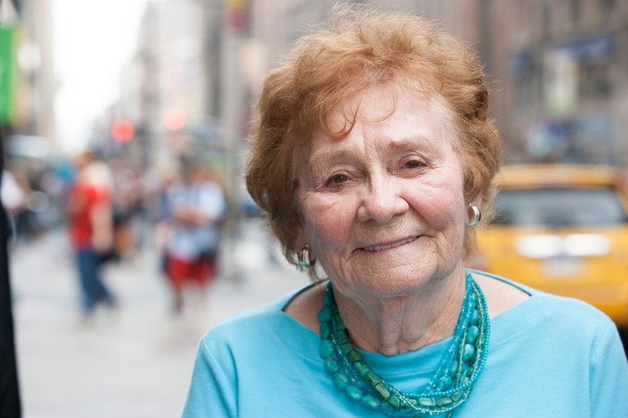Senior woman on a city street with a taxi in the background