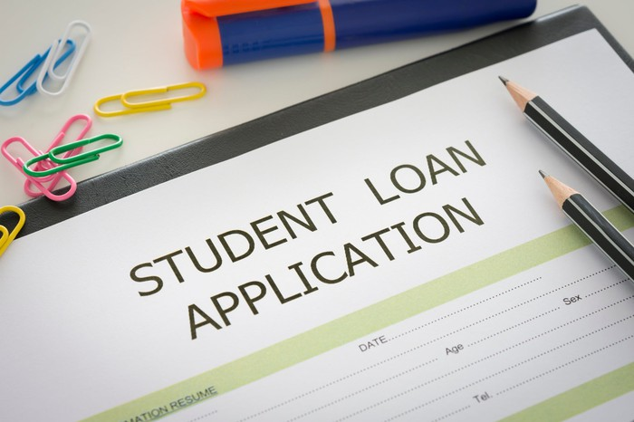 A student loan application on a desktop with pencils and paper clips.